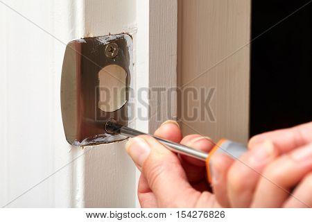 Door strike plate installation.