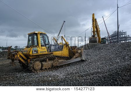 Tobolsk, Russia - July 15. 2016: Sibur company. Construction of plant on processing of hydrocarbonic raw materials. Bulldozer moves gravel on construction site in rainy weather