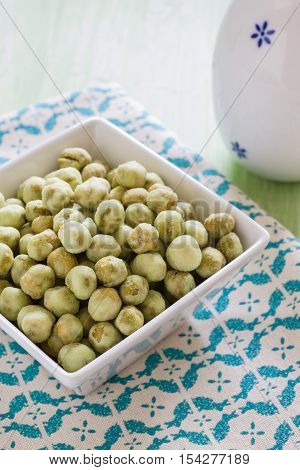 Wasabi peas a Japanese snack made with roasted crunchy green peas coated with wasabi seasoning in a modern white ceramic bowl