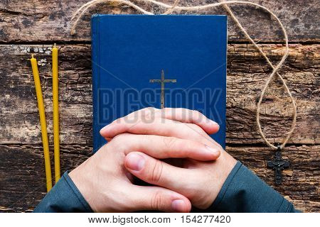 man praying on the bible on wooden background