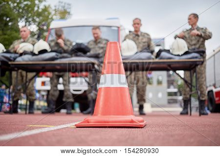 MOSCOW, RUSSIA - AUG 20, 2016: Red protective cone and firefighters team at background during the Moscow City Championship of combat deployment in Luzhniki.