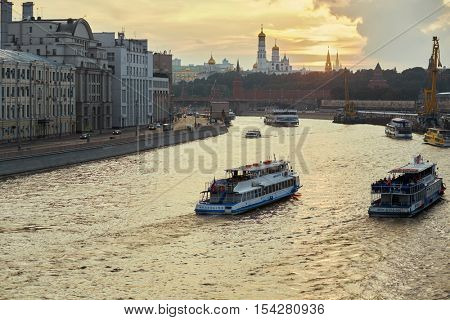 MOSCOW, RUSSIA - AUG 20, 2016: Pleasure boats with inscriptions Moscow at Moskva River and the Kremlin during sunset.