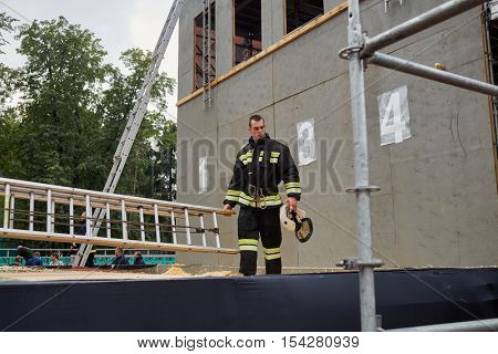 MOSCOW, RUSSIA - AUG 20, 2016: Firefighter stand next to the dummy building during the Moscow City Championship of combat deployment in Luzhniki.