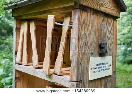 MOSCOW, RUSSIA - JUN 18, 2016: Wooden beehive in Izmailovskaya apiary among plants on summer day. This is a firsrt movable-frame hive in the world by P.I.Prokopovich (inscription on plate).