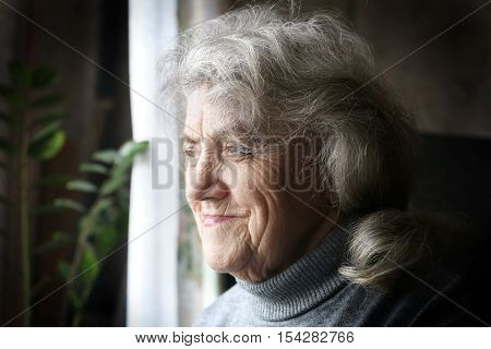 Grandmother face. Old woman portrait over dark
