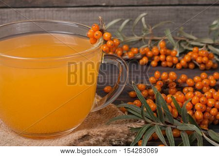 Tea of sea-buckthorn berries with a sprig on sackcloth.
