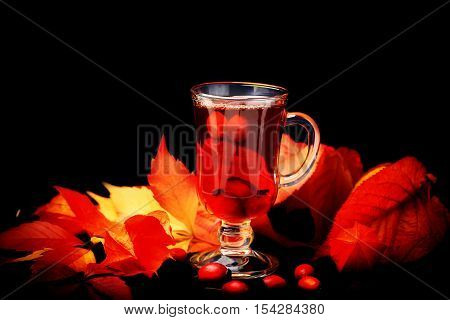 Therapeutic hot tea with a dogrose on a wooden background retro rustic style physalis in a basket
