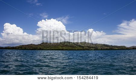 An island in the distance with puffy clouds over it.