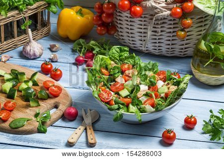 Preparing a healthy spring salad on wooden table