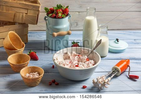 Ingredients for homemade strawberry ice cream on wooden table