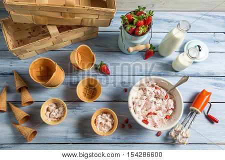 Homemade production of strawberry ice cream on wooden table