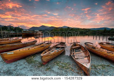 Stunning sunset over wooden rowing boats on Derwentwater at Keswick in the Lake District Nationla Park in Cumbria