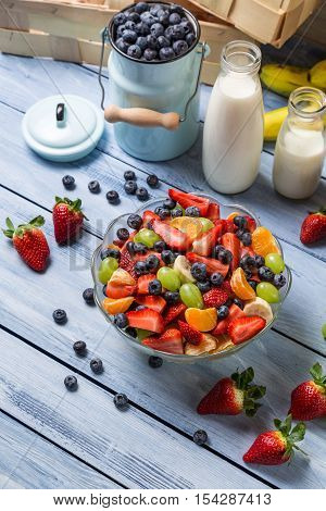 Preparing a healthy spring fruit salad on wooden table