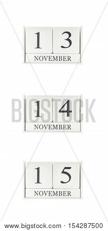 Closeup group of white wooden calendar with black 13 14 15 november word three date calendar isolated on white background