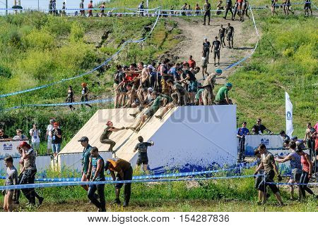 Tyumen, Russia - July 9, 2016: Steel Character extrim race on Voronino Hill. People run on inclined wall and jump to water