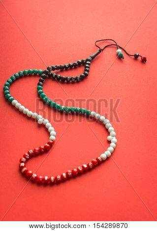 An Islamic rosary with beads in national flag colors of UAE on red background. Top view.