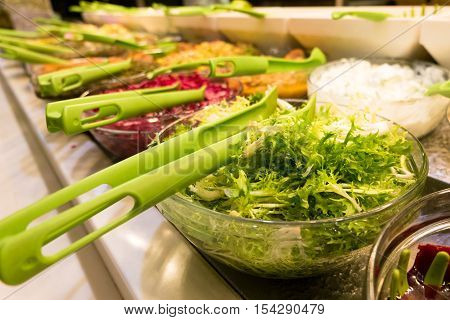 Salad bar with selective focus on the green vegie bowl