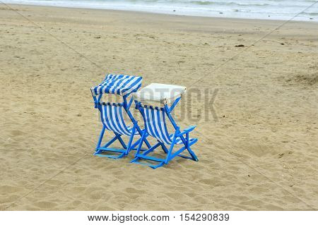 Two deck chairs on the beach at Sandown on the Isle of Wight