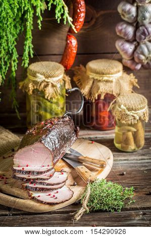 Rural smokehouse with ham and herbs on old wooden table