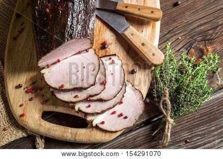 Freshly smoked ham with marjoram on old wooden table