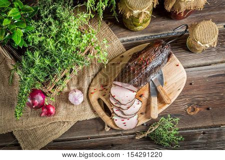 Fresh smoked ham in pantry on old wooden table