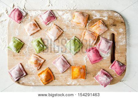 Multi-colored ravioli on a cutting board, sprinkled with flour, cooking process, on a white table. Funny food for children. View from above