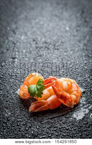 Closeup of fresh shrimp on a black rock
