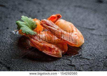 Closeup of shrimp served on black rock