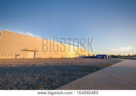 Parking area outside big warehouse. Empty space for your object placement. Urban, industrial theme.