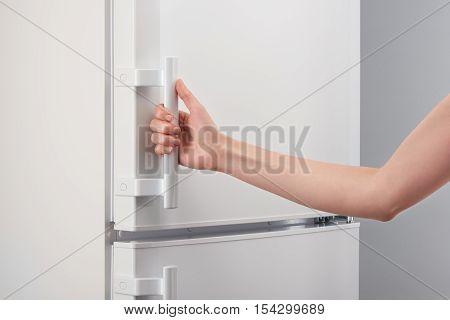 Female Hand Holding Handle Of White Refrigerator Door