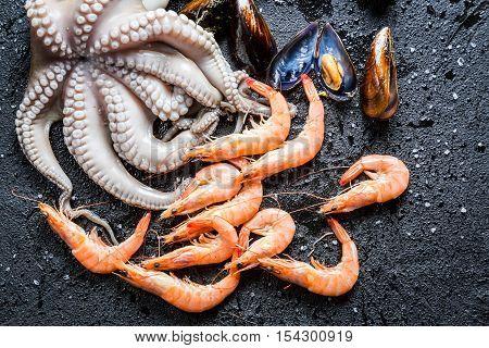 Closeup of three kinds fresh seafood on black rock