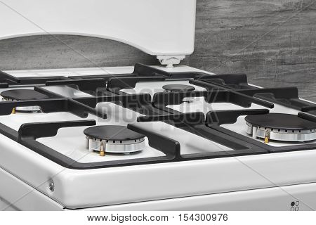 Close Up Of Clean White Kitchen Gas Stove On Gray
