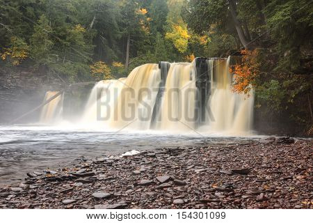 Manabezho Falls on the Presque Isle River in the Upper Peninsula of Michigan surrounded by autumn colors on a misty morning