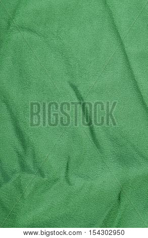 Green wrinkled fabric texture background. Close up