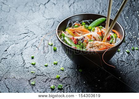 Rice noodles with vegetables and prawns on black rock
