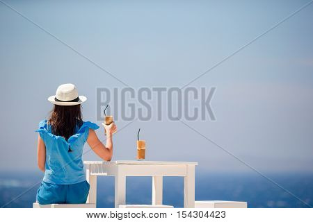 Young woman drinking cold coffee enjoying sea view.