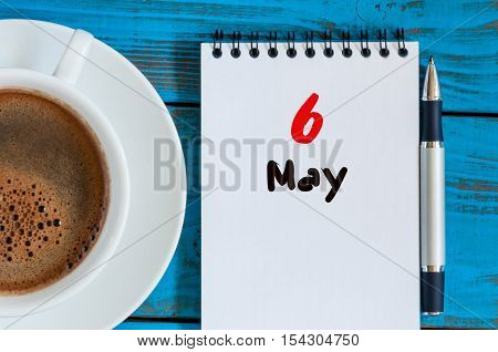 May 6th. Day 6 of month, calendar on white notepad with morning coffee cup at work place background. Spring time, Top view.