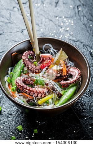 Traditional dish with octopus and noodles on black rock