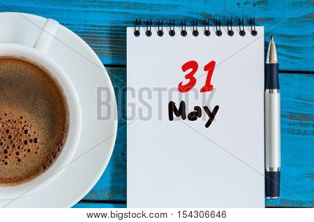 May 31st. Day 31 of month, calendar on white notepad with morning coffee cup at work place background. Spring time, Top view.