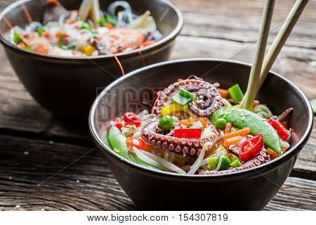 Noodles with vegetables and seafood on old wooden table