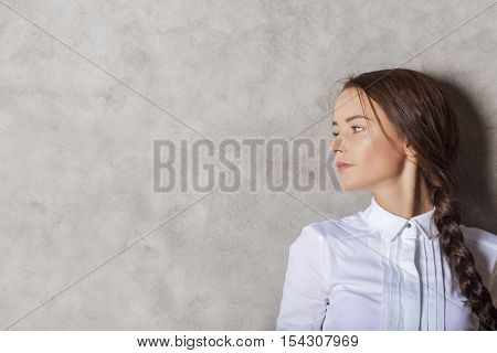 Portrait of attractive caucasian businesslady on textured concrete wall background with copy space