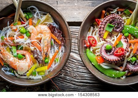 Two dishes with vegetables and seafood on wooden table