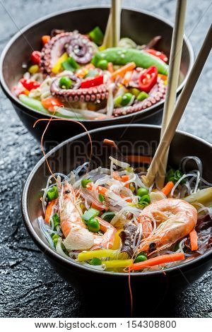 Seafood and vegetables served with noodles on black rock