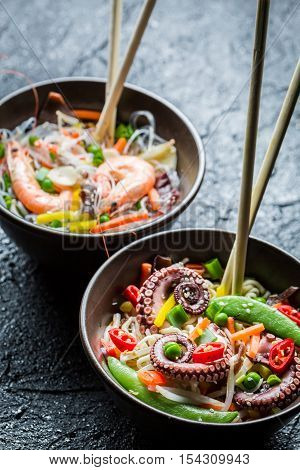 Traditional dish with seafood and noodles on black rock