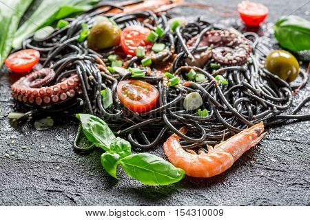 Closeup of black spaghetti with prawn on black rock