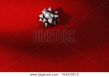 Red fabric closeup background with shadow, waves and visible texture or pattern.