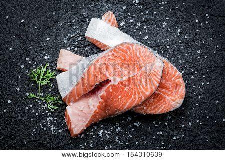 Closeup of fresh raw salmon on black rock