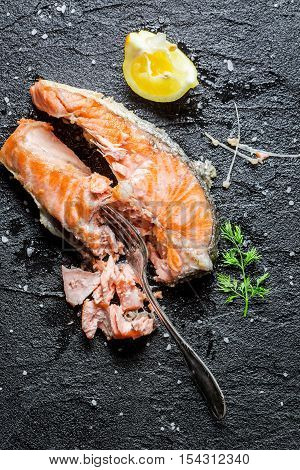 Freshly fried salmon served with lemon on black rock