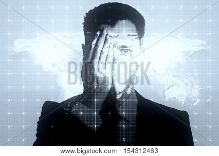 Young businessman closing one eye with hand on light mesh background with map