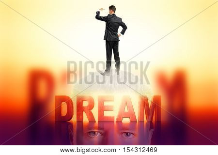 Dream concept. Standing businessman with abstract text